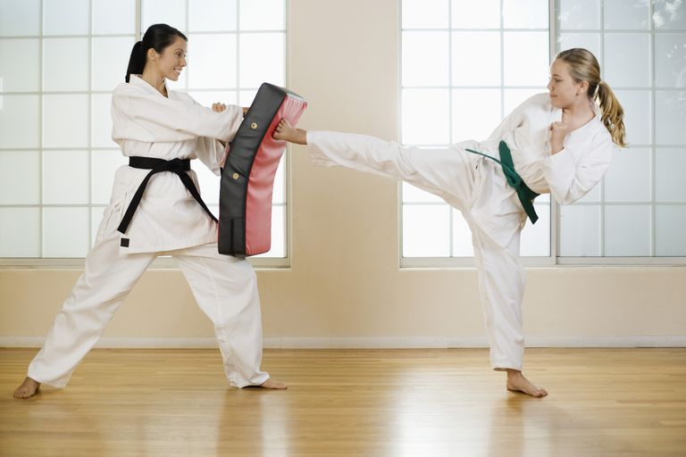 An Image showing a young girl trying to defending her opponent by holding an equipment.