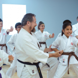 Image showing happy coach given karate training to his students in a training session.