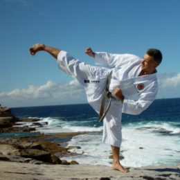 A Man Doing karate Stance In A Beach Shore.