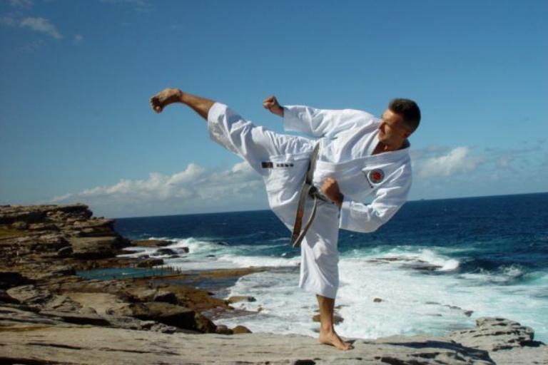 A Man Doing karate Stance In A Beach Shore.