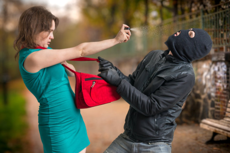 A Woman Defending A Robber By Pepper Spray.