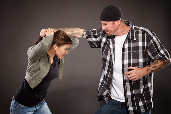 A Young Woman Defending The Person Who Pulling Her Hair.